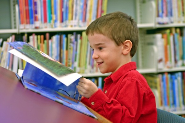 boy reading library